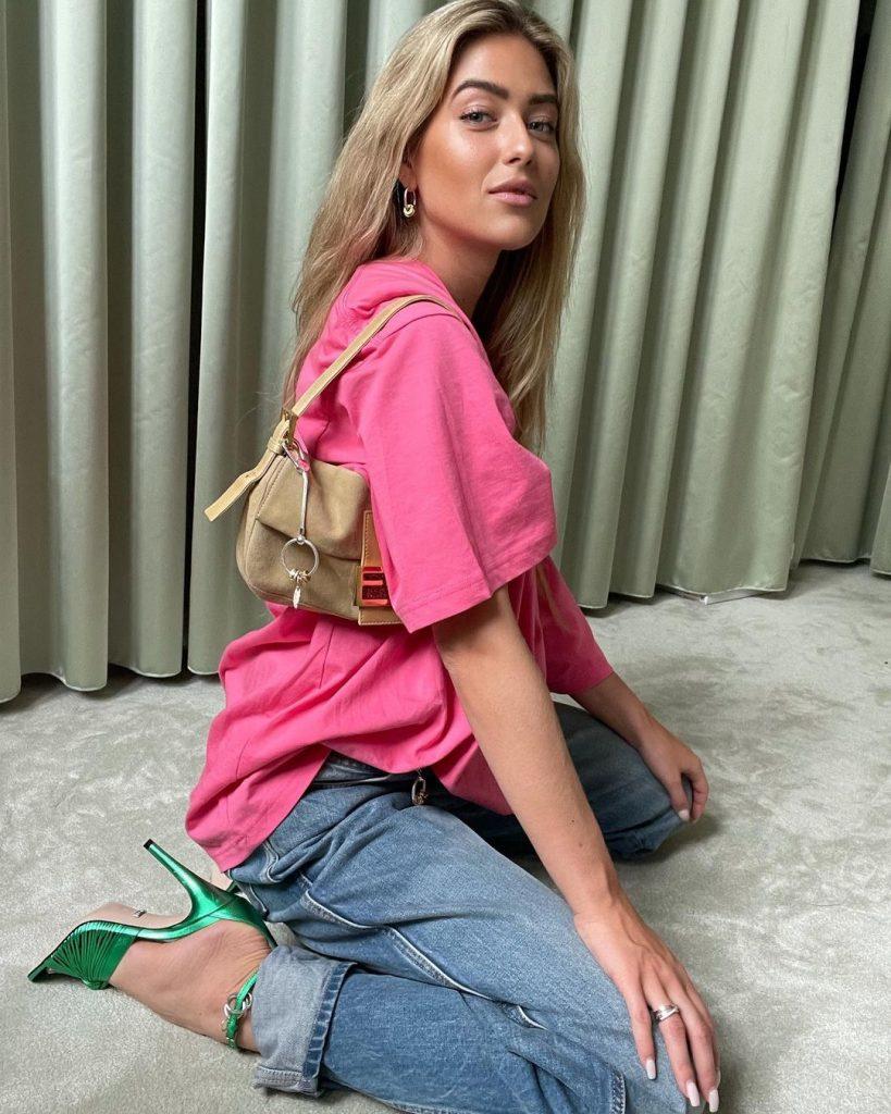 Foto Emili Sindlev usando um look com jeans + camiseta + acessórios statement com cores mais saturadas